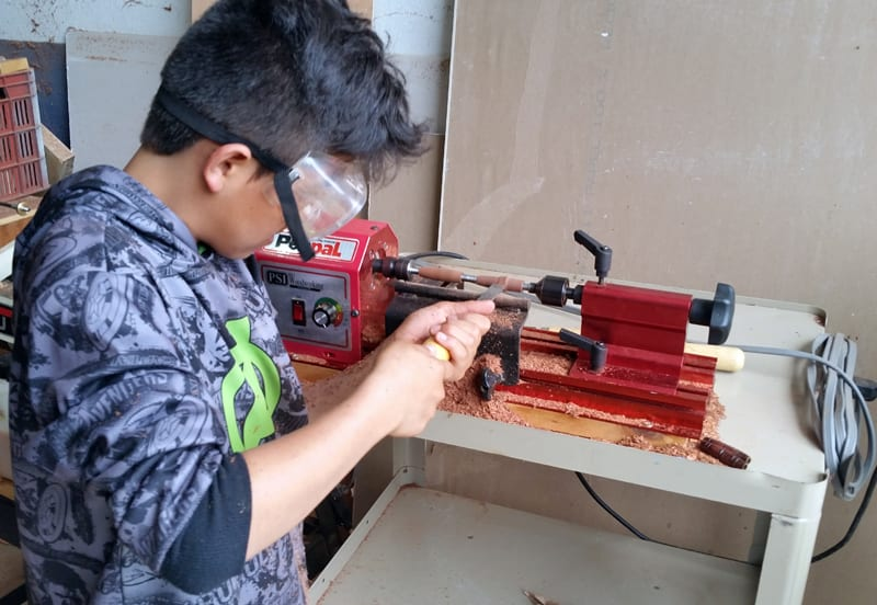 Students from the orphanage Fundaninos making wooden pens on a lathe